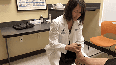 Dr. Davis examines a patient to determine if flat foot reconstruction is necessary.