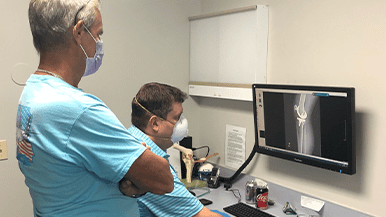 Specialists at Orlando Orthopaedic Center review x-rays for a bilateral total knee replacement.